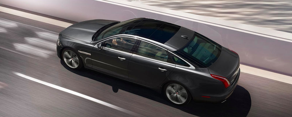 Gray Jaguar XJ driving on highway