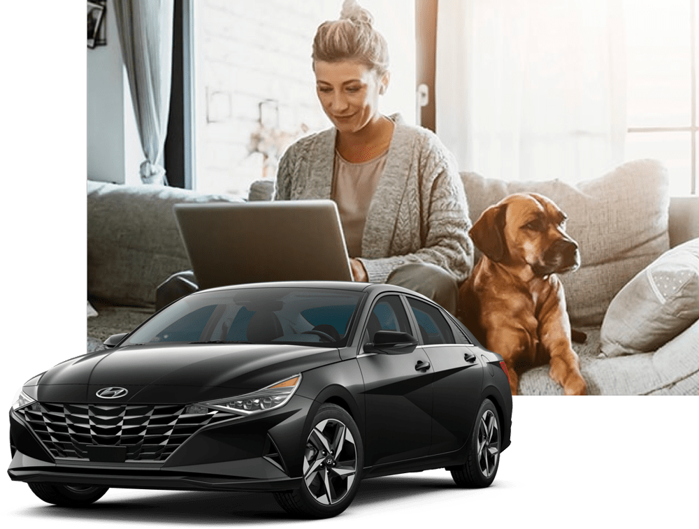 A woman siting on her couch on her laptop with a dog next to her and a black sedan vehicle