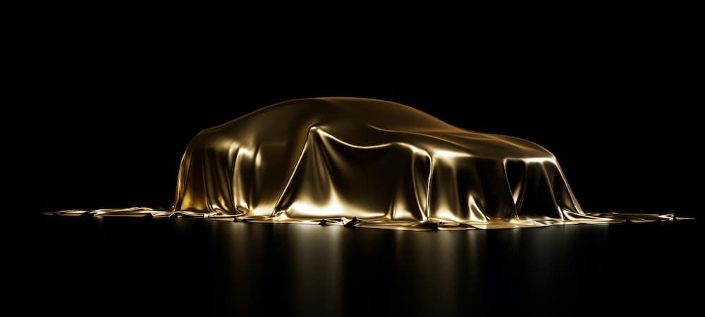 Car Hidden By Golden Sheet on Black Background