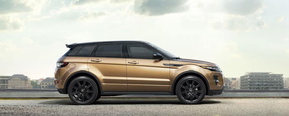 2019 Range Rover Evoque side view in gold parked in a city next to a river