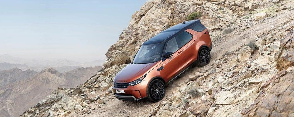 2019 land rover discovery descending down a rocky hill
