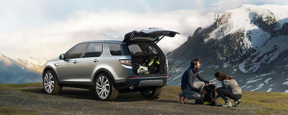 2019 Land Rover Discovery Sport parked in mountains with people unpacking