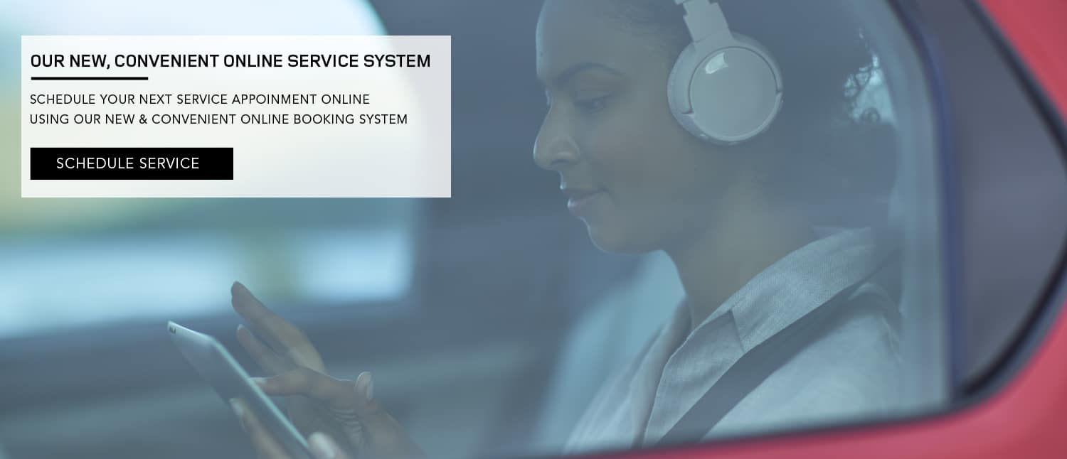 OUR NEW, CONVENIENT ONLINE SERVICE SYSTEM. SCHEDULE YOUR NEXT SERVICE APPOINMENT ONLINE USING OUR NEW CONVENIENT ONLINE BOOKING SYSTEM. SCHEDULE SERVICE. WOMAN VIEWING PHONE AS A PASSENGER IN A VEHICLE.