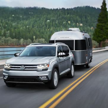 Silver 2018 Volkswagen Atlas towing trailer on highway with forested hills in background