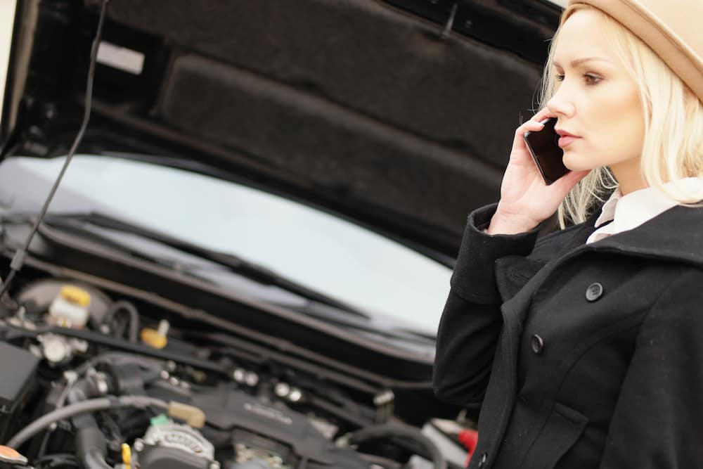 Attractive trendy young blond woman calling roadside assistance for her vehicle after suffering a break down, side view talking on her mobile