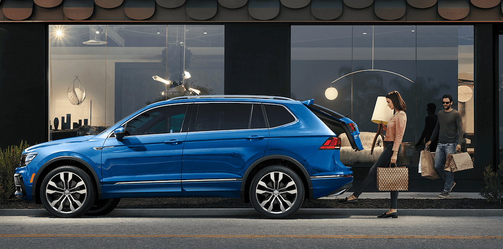 2020 Volkswagen Tiguan on city street with woman loading trunk cargo