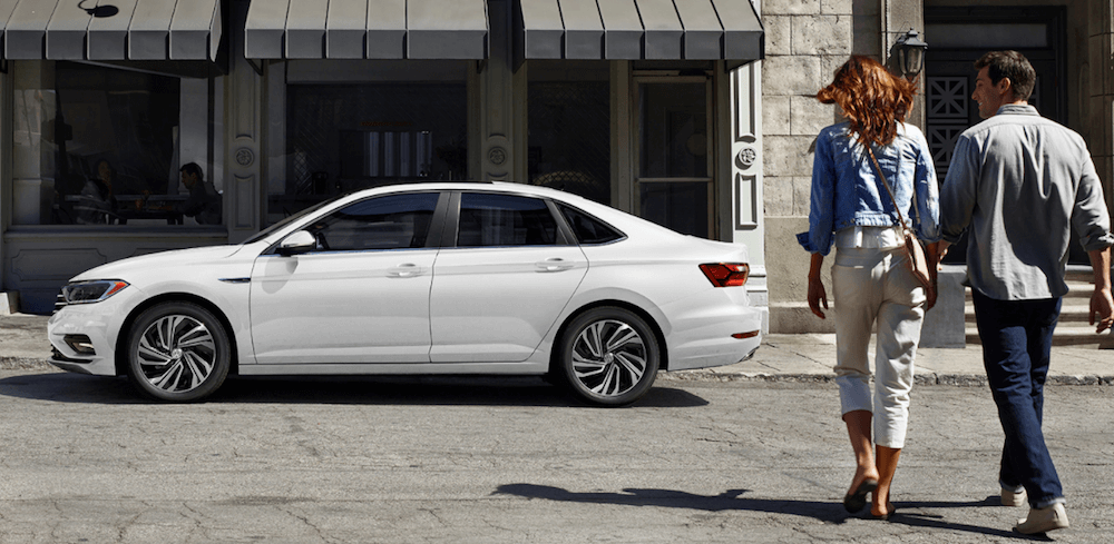 2020 VW Jetta parked on city street with couple nearby