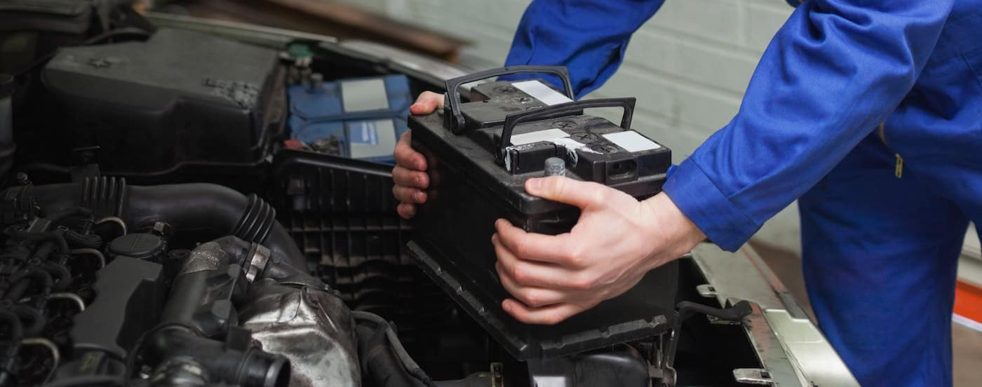 Mechanic checking car battery in workshop