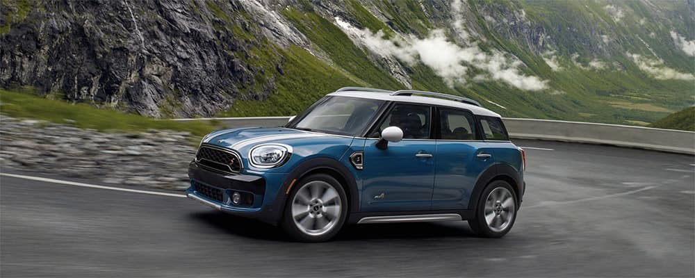 Image of a Mini Countryman driving on a windy road through the mountains.