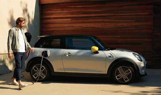 MINI SE parked in a driveway with a man walking up to it.