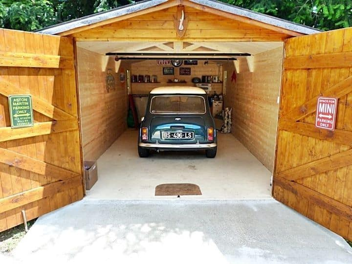 Classic MINI Cooper in an outdoor garage.