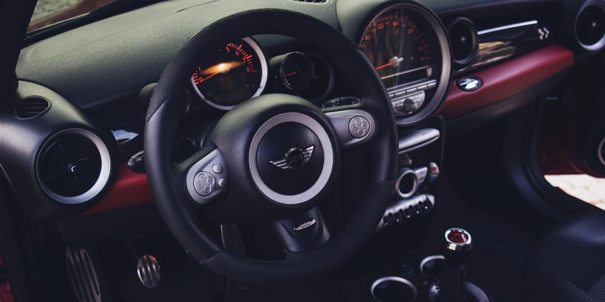 Photo of the inside of a MINI Cooper, focused on the steering wheel and brand emblem.
