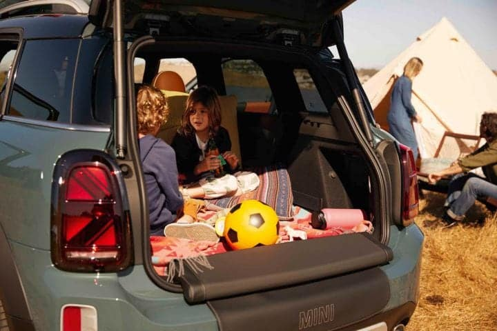 Kids sitting in the cargo area in a new 2021 MINI Countryman SAV while camping.