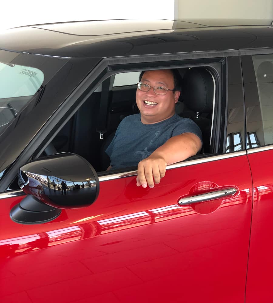 One of our Client Advisors sitting in his brand new red MINI Cooper S.