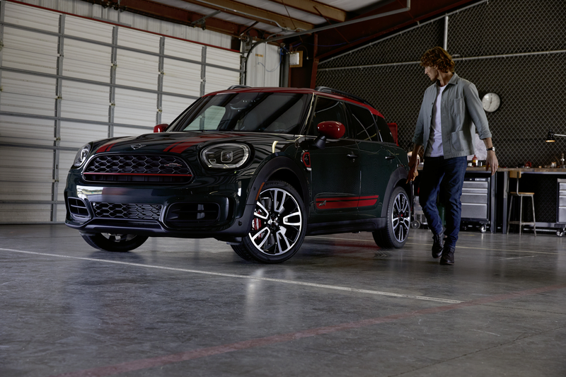 F60 John Cooper Works in a garage with a man walking beside it.