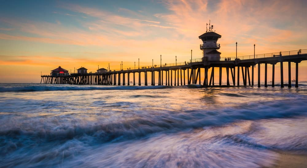 A Huntington Beach pier against a vibrant sunset for nearby Ram Dealers in Orange County