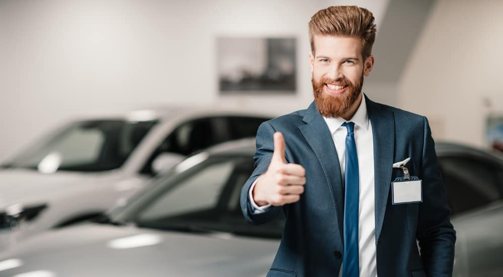Car salesman with beard and thumbs up