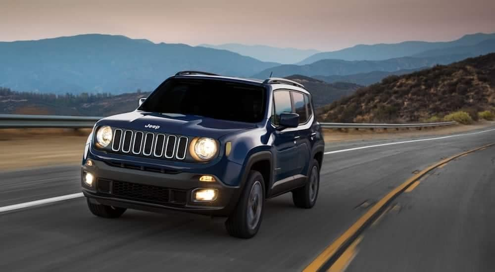 A blue 2019 Jeep Renegade drives on a quiet California mountain road