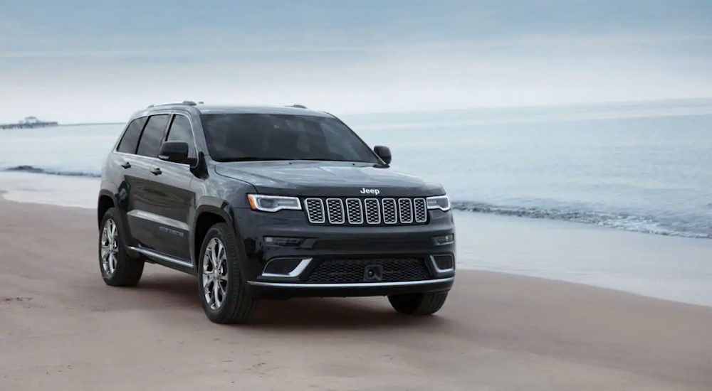 A black Jeep Grand Cherokee from a Jeep Dealership in Orange County drive on the beach