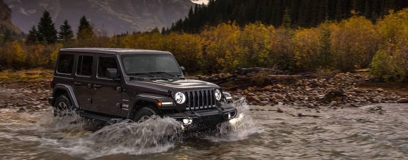 A black Jeep Wrangler crosses a deep river
