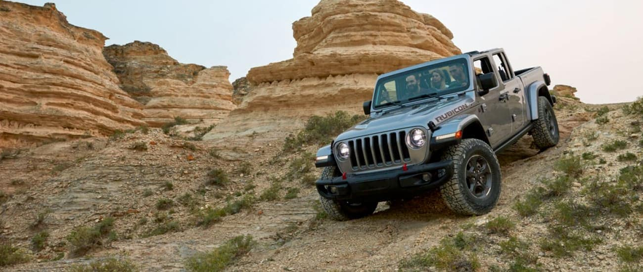 A silver 2020 Jeep Gladiator is off-roading with passengers on a desert trail.