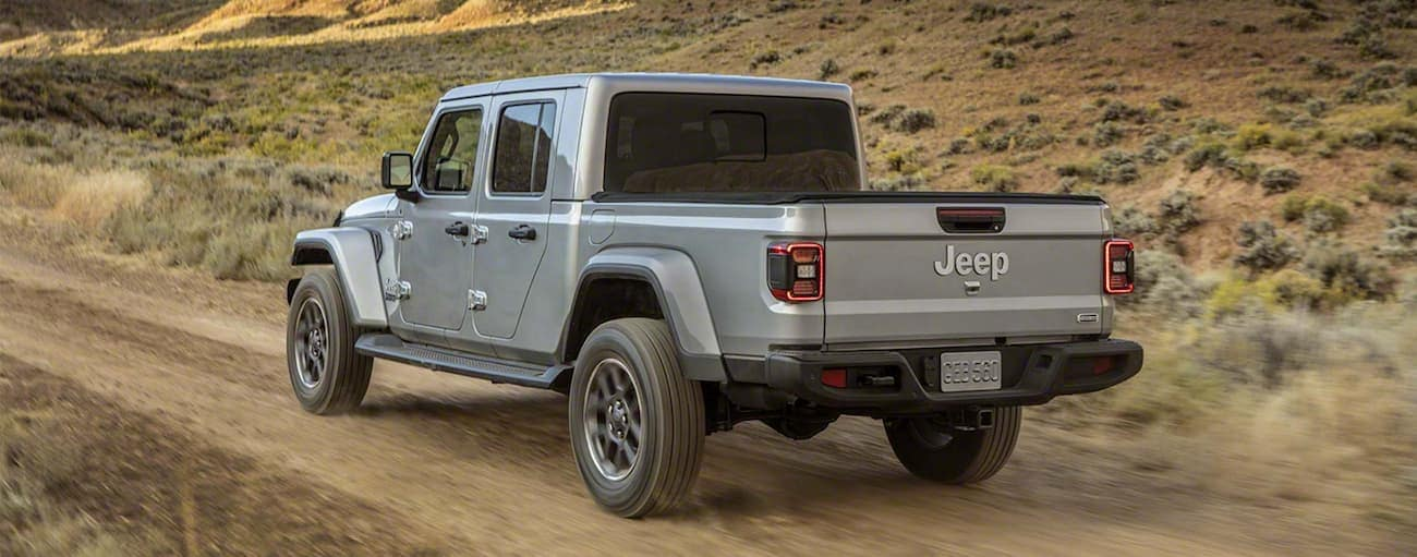 A grey 2020 Jeep Gladiator is driving on a dirt road outside Costa Mesa, CA.