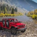 A new red 2020 Jeep Gladiator crosses a large river at the foot of a mountain