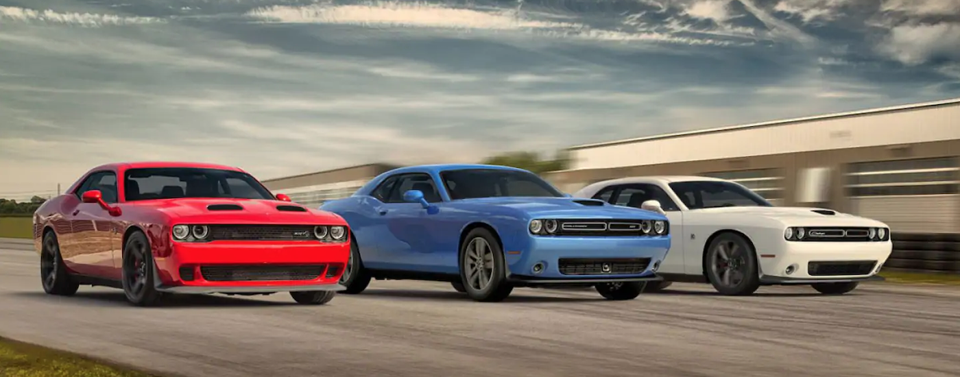 Three 2019 Dodge Challengers in red, white, and blue are racing on a track