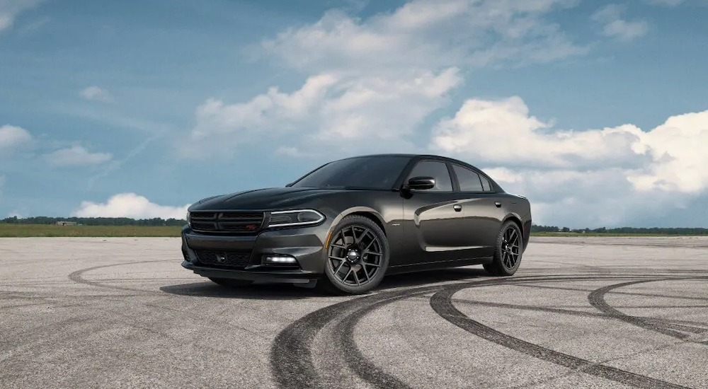 A 2019 black Dodge Charger is surrounded by tire marks from drifting on the pavement. Chargers are popular at Orange County Dodge Dealers.