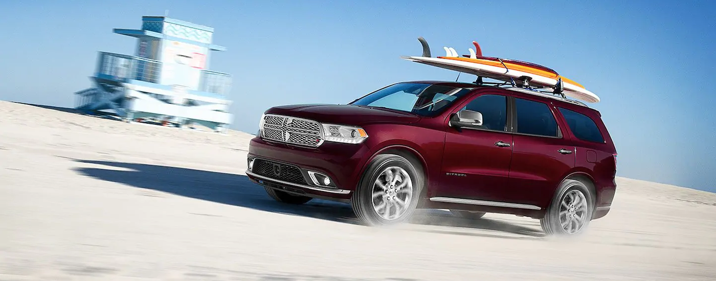 A 2019 burgundy Dodge Durango with a surfboard on the roof is driving on the sand at the beach.