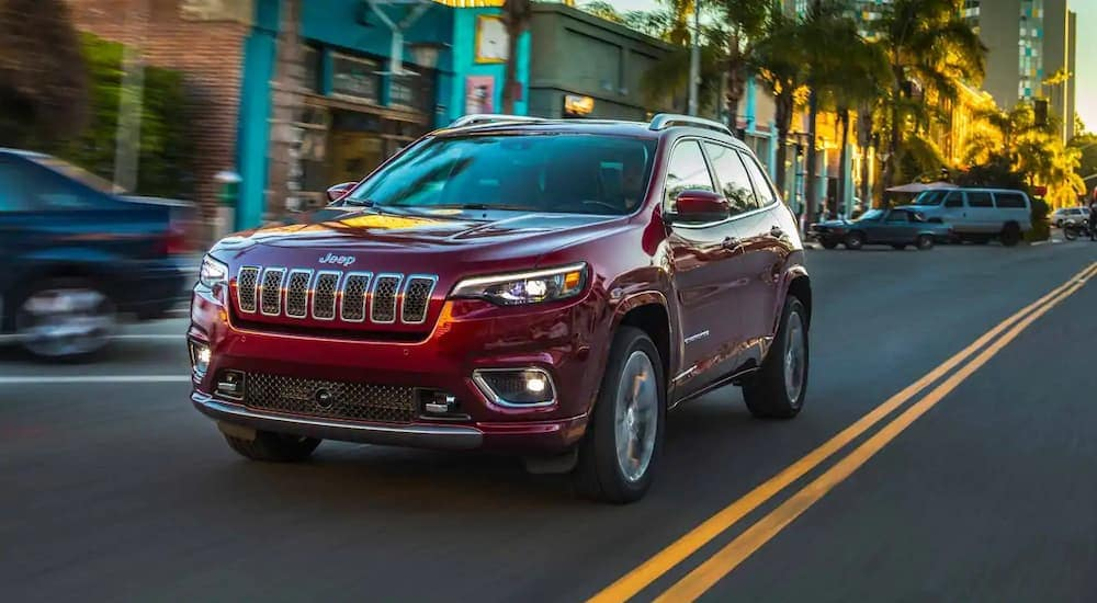 A burgundy 2019 Jeep Cherokee is driving away after finding jeep lease deals in Costa Mesa, CA.