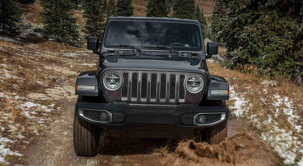 A 2019 Jeep Wrangler is driving in the mud after checking out Jeep lease deals in Costa Mesa, CA.