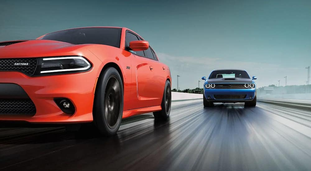 An orange 2018 Dodge Charger is racing a blue Challenger on a wet track. Oranger County Dodge Dealers are a great place to check one out.