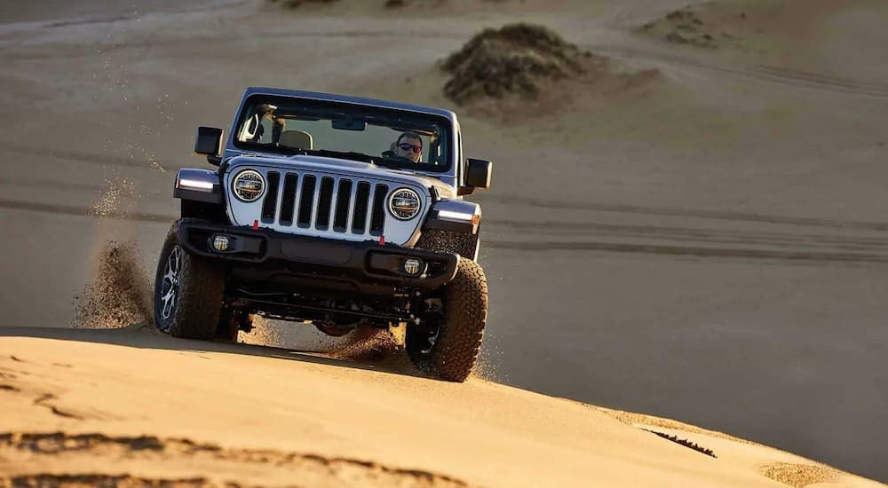 A silver 2019 Jeep Wrangler Rubicon is driving on the sand near Costa Mesa, CA.