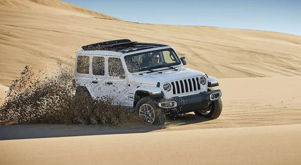 A white 2019 Jeep Wrangler Sahara, acquired through Jeep lease deals, is driving on the sand near Costa Mesa, CA.