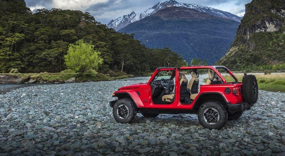 A red 2019 Jeep Wrangler is shown parked on rocks in the woods on a cloudy day. You could find this Jeep for sale near Costa Mesa, CA.