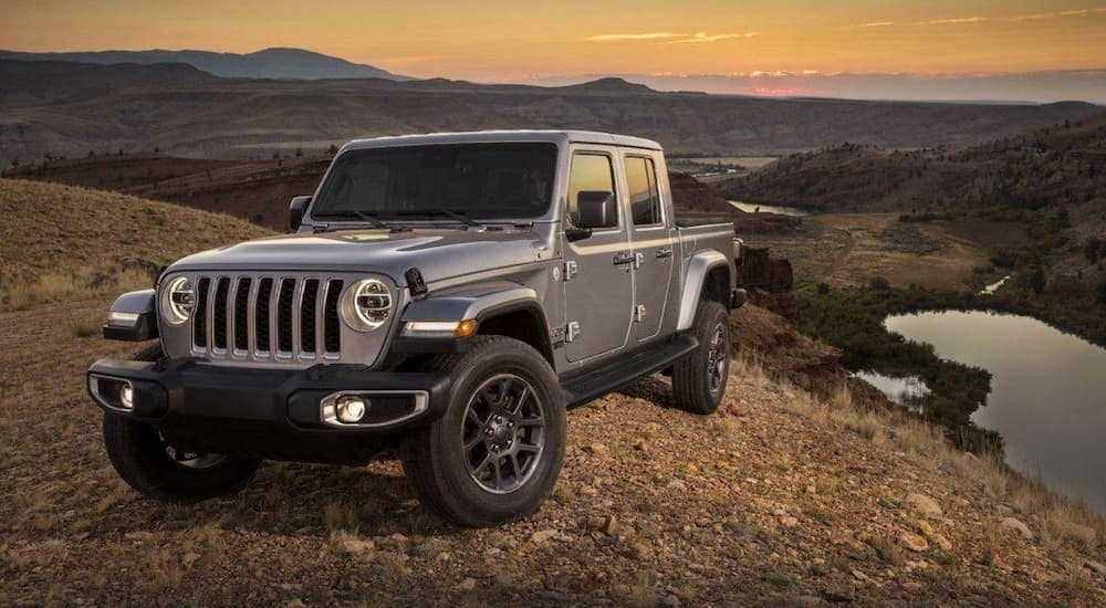 A grey 2020 Jeep Gladiator is parked high up with mountains in the distance and a setting sun.