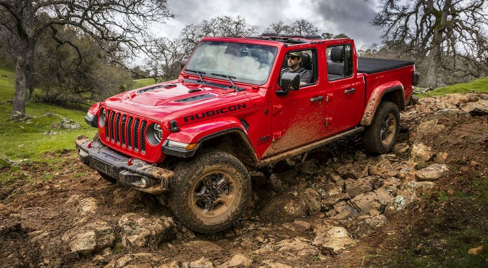 A red 2020 Jeep Gladiator is climbing over mud and rocks on a trail outside Costa Mesa, CA.