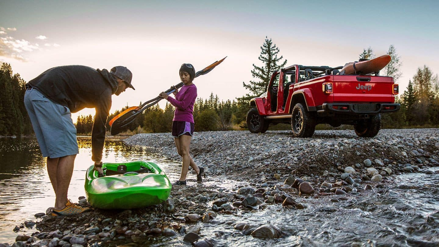 A red 2020 Jeep Gladiator with two Kayakers next to a river