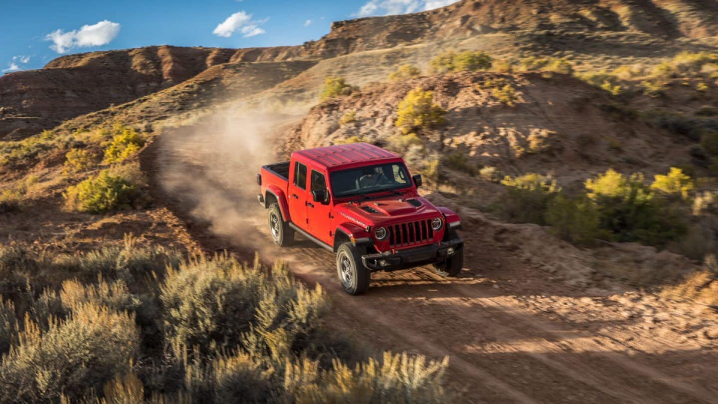 A red 2020 Jeep Gladiator driving on a mountain dirt road
