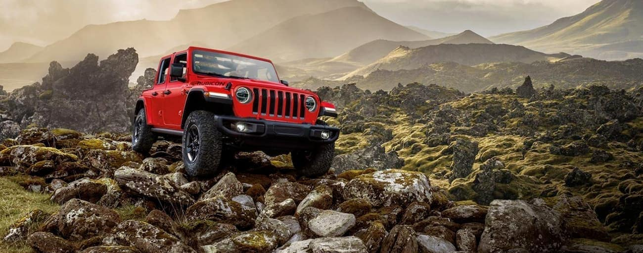 A red 2020 Jeep Wrangler is off-roading on a rocky trail.