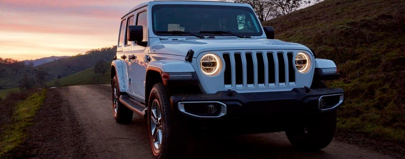 A white 2020 Jeep Wrangler is driving at dusk near Costa Mesa, CA.