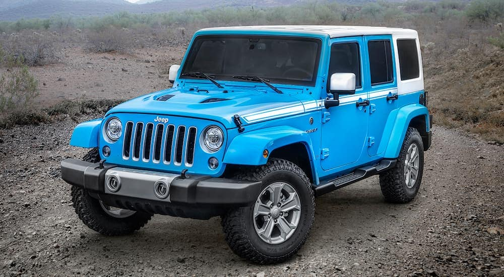 A blue and white 2017 Jeep Wrangler is a certified pre-owned vehicle in Costa Mesa, CA, is parked on a gravel road.