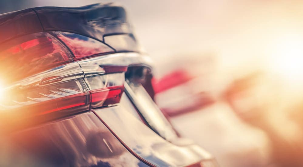 A closeup of the tailgates of used cars in a row with a sun glare.