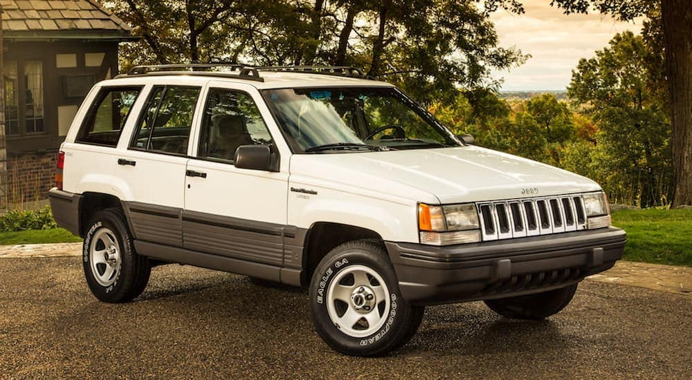 A white 1998 Jeep Grand Cherokee, which is a favorite at your local used car dealer in Costa Mesa, CA, is parked next to a home.