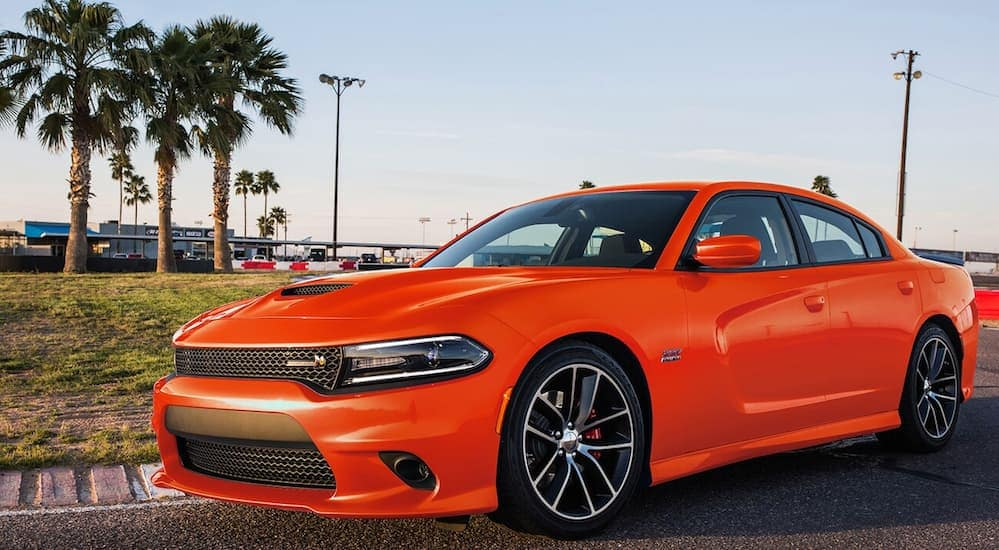 An orange 2017 Dodge Charger R/T is parked next to a racetrack at dusk near Costa Mesa, CA.