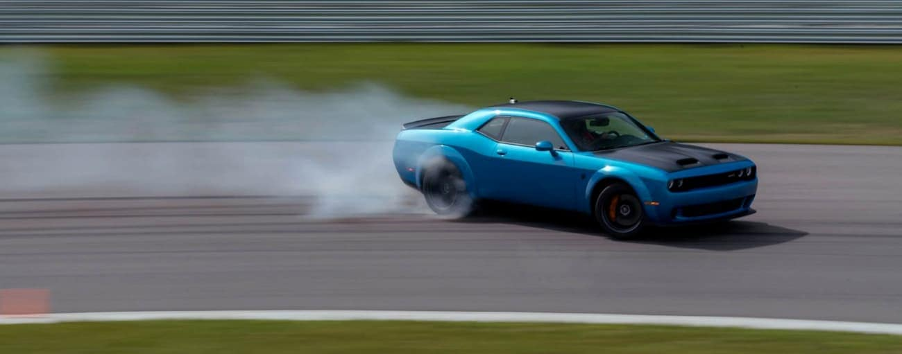 A blue 2020 Dodge Challenger is drifting around a track near Costa Mesa, CA.