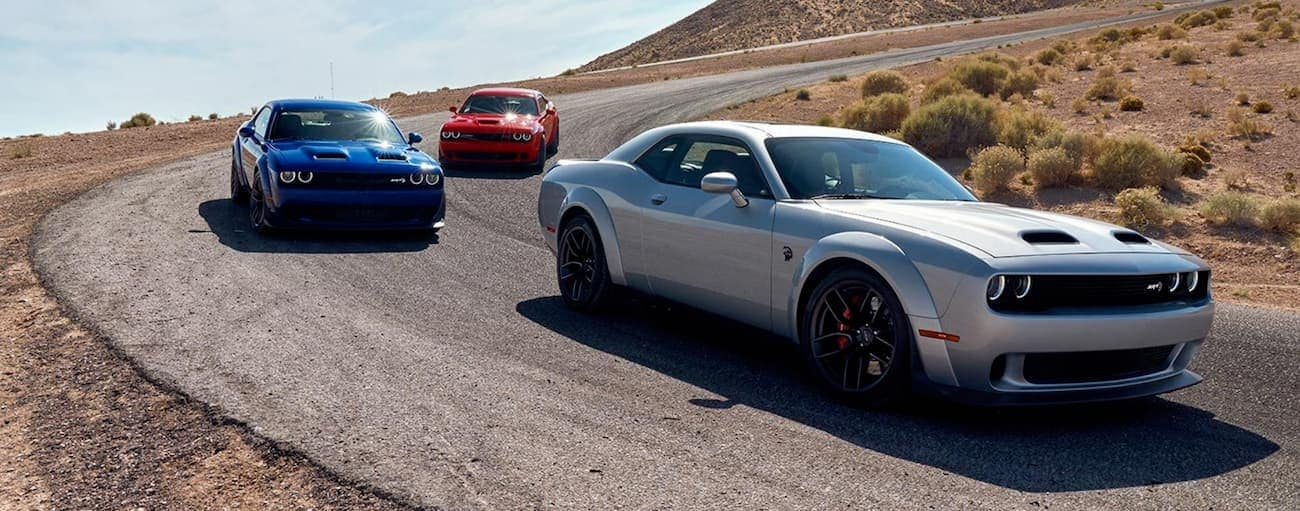 A silver 2020 Dodge Challenger is being followed by a red and a blue Challenger on a curvy desert road.