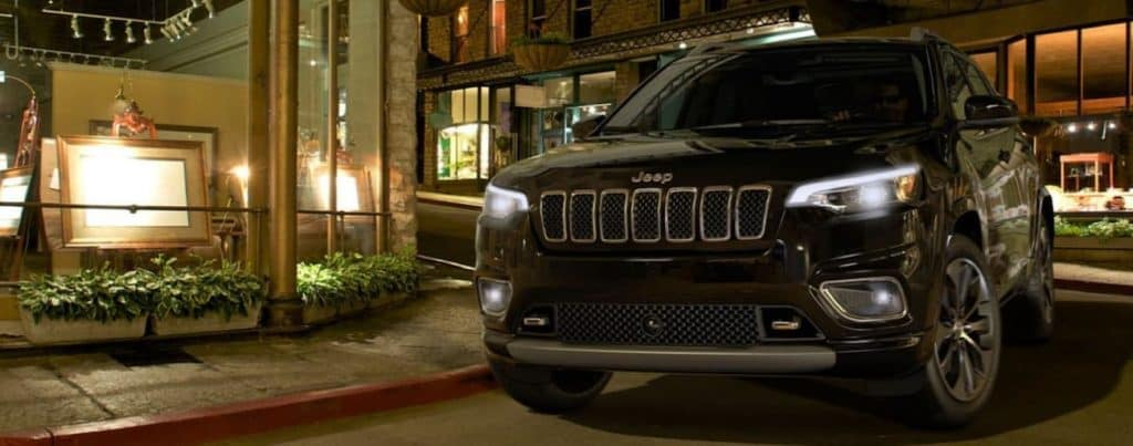 A black 2020 Jeep Cherokee is parked in front of a lit up store front on a city street near Costa Mesa, CA.