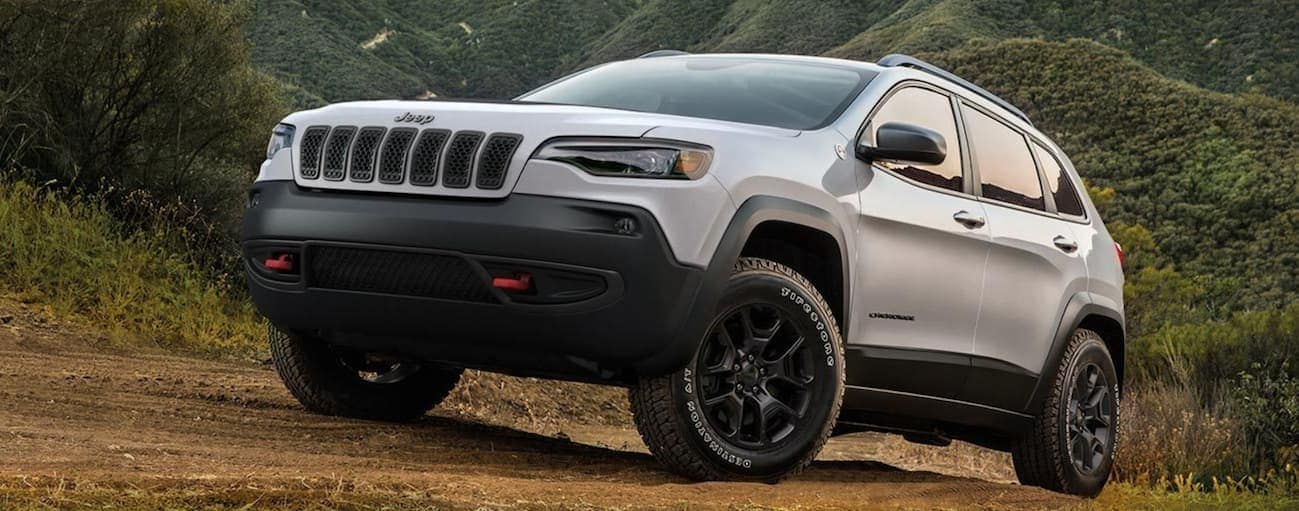 A white 2020 Jeep Cherokee is driving on a dirt hill with green mountains in the distance.